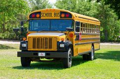 Autobús escolar del campamento de verano en campo de hierba fotografía de archivo libre de regalías