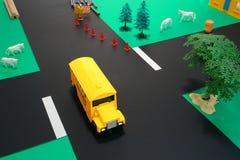 Autobús escolar del juguete de la educación del programa piloto en el camino peligroso Foto de archivo