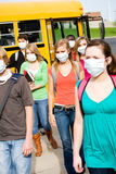 Autobús escolar: Grupo de estudiantes que llevan mascarillas Foto de archivo libre de regalías