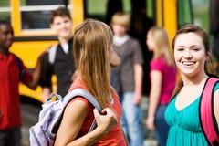 Autobús escolar: Muchacha que ríe cuando Guy Flirts con ella Imágenes de archivo libres de regalías