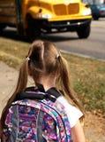 Autobús escolar que espera de la muchacha para imagenes de archivo
