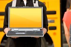 Autobús escolar: Sostener el ordenador portátil con la pantalla en blanco Fotos de archivo