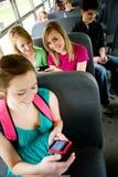 Autobús escolar: Usando un teléfono elegante en el autobús Fotografía de archivo