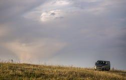 Autobús gris en el prado debajo del cielo hermoso foto de archivo