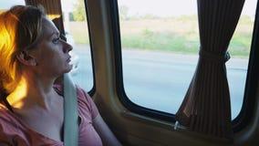 Autobús pensativo triste del montar a caballo de la muchacha y mirada hacia fuera de la ventana fotografía de archivo
