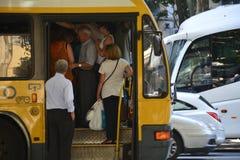 Autobús que entra de la muchedumbre foto de archivo