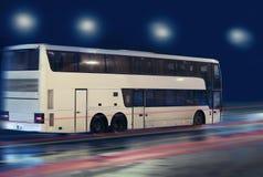 Autobús que mueve encendido la ciudad de la noche Imagenes de archivo