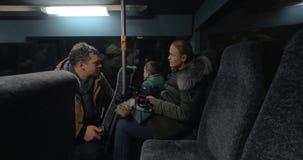 Autobús que viaja de la mamá, del papá y del hijo por la tarde y los teléfonos móviles con metrajes