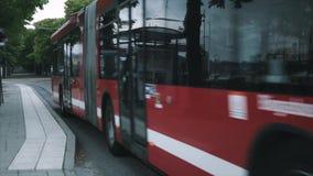 Autobús rojo de la ciudad que conduce abajo de una calle almacen de video