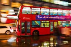 Autobús rojo del autobús de dos pisos en la falta de definición de movimiento en tráfico de la noche de Londres Foto de archivo libre de regalías