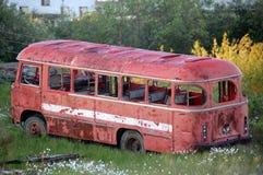 Autobús rojo roto abandonado en la ciudad de Chersky Imágenes de archivo libres de regalías
