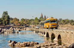 Autobús turístico amarillo que conduce a través del puente de piedra estrecho en el río Imagen de archivo