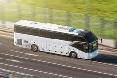 Autobús turístico que apresura en la carretera, blured en el movimiento foto de archivo