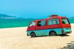 Autobús viejo en la arena de la playa con el fondo azul del mar foto de archivo