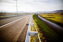 Autobahn auf szenischen grünen Wiesen einer sonniger Tagesabflussrinne Reisende Langstrecke der Autobahn Asphaltlandstraßenstraße Stockfoto