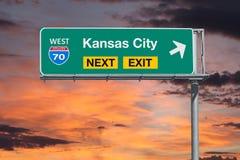 Autobahn-folgendes Ausgangs-Zeichen Kansas City-Weg-70 mit Sonnenuntergang-Himmel Stockfoto