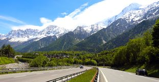 Autobahn at the mountains. Straight autobahn going to the mountains at the sunny day stock image