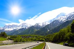 Autobahn at the mountains. Straight autobahn going to the mountains at the sunny day royalty free stock photo