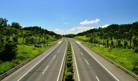 Autobahn, weiße Wolken und blauer Himmel Stockfotografie