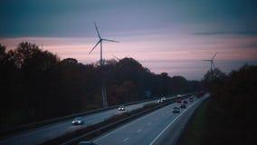 Autobahn y molinoes de viento para la energía eléctrica en fondo del cielo de la puesta del sol almacen de video