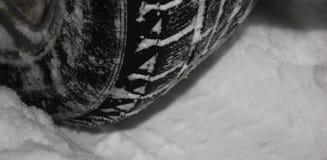 Autobanden op de winterweg met sneeuw wordt behandeld die stock afbeelding