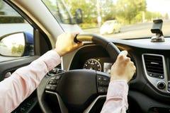 Autobinnenland met vrouwelijke bestuurderszitting achter het wiel, zacht zonsonderganglicht Luxueus voertuigdashboard en elektron stock foto