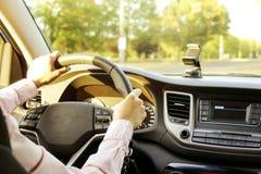 Autobinnenland met vrouwelijke bestuurderszitting achter het wiel, zacht zonsonderganglicht Luxueus voertuigdashboard en elektron royalty-vrije stock fotografie