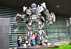 Autobot and kids. Some kids are around the magic autobot standing in front of gate. Taken at the Chana Auto Exhibition in Chongqing Science and Technology Museum Royalty Free Stock Images