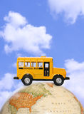 Autobús escolar en el globo Imagenes de archivo