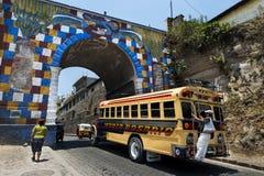 Autobus avec un homme se tenant sur une barre dans le dos entrant dans la ville de Chichicastenango, au Guatemala Photos stock