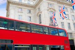 Autobus de Londres et drapeaux du R-U dans le cirque de Piccadilly Photo stock