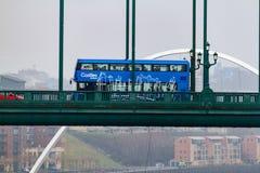 Autobus a due piani blu che attraversa Tyne Bridge ed il Br di millennio Fotografia Stock