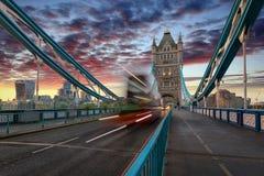 Autobus a due piani rosso che attraversa il ponte della torre a Londra immagine stock