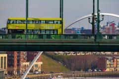Autobus a due piani verde che attraversa Tyne Bridge ed il millennio B Immagini Stock