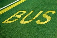 Autobus pisać na zieleń asfalcie Obraz Royalty Free