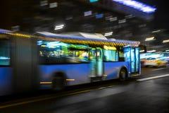 autobus rusza się wzdłuż alei przy nocą w deszczu Zdjęcia Stock