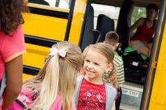 Autobus scolaire : Filles parlant sur le point d'avoir l'autobus Image stock