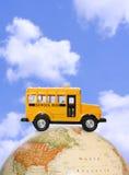Autobus scolaire sur le globe Images stock