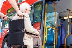 Autobus supérieur d'embarquement de couples utilisant la bretelle d'accès de fauteuil roulant Photographie stock libre de droits