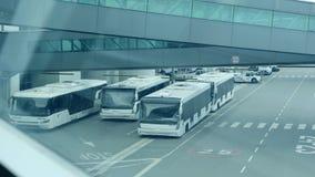 Autobuses de lanzadera del aeropuerto parqueados cerca del terminal de aeropuerto metrajes