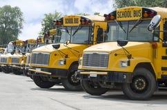 Autobuses escolares alineados para transportar a niños Imágenes de archivo libres de regalías