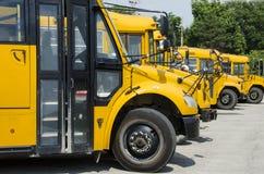 Autobuses escolares alineados para transportar a niños Fotos de archivo