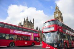 Autobuses rojos delante de casas del parlamento imágenes de archivo libres de regalías