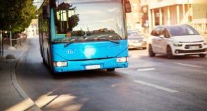 Autobusowy poruszający na drodze w mieście w wczesnym poranku Zdjęcie Royalty Free