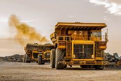 Autocarri con cassone ribaltabile di estrazione mineraria che trasportano il minerale metallifero del platino per elaborare fotografia stock libera da diritti