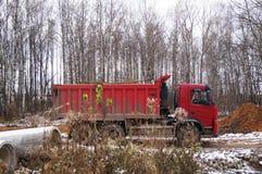 Autocarro con cassone ribaltabile automobilistico rosso sul lavoro fotografia stock