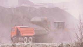 Autocarro con cassone ribaltabile di caricamento dell'escavatore con la sabbia ad una cava della sabbia stock footage