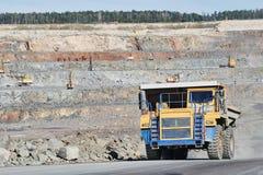 Autocarro con cassone ribaltabile enorme che trasporta la roccia o il minerale di ferro del granito Fotografia Stock