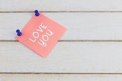 Autocollant de papier avec le texte : amour que vous avez goupillé sur la table en bois Photos libres de droits