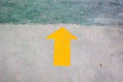 Autocollant jaune de flèche sur le plancher avec l'espace de copie Images libres de droits